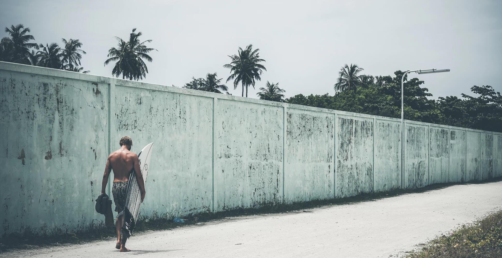 Fotografía de surfista andando con una tabla en el brazo
