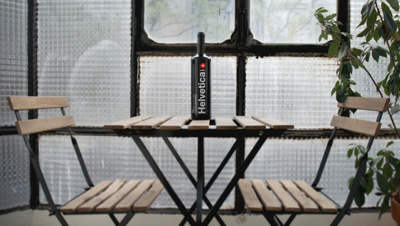 Fotografía de la botella de Helvetica Wine sobre una mesa