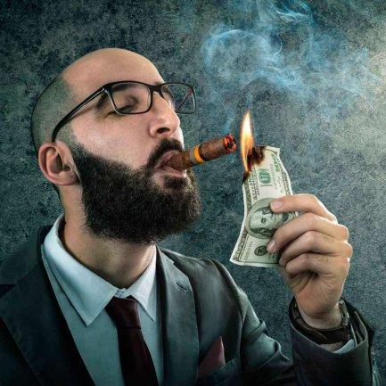 Hombre quemando dólares con un puro