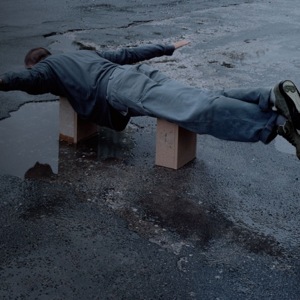 Señor con traje tumbado sobre cajas de cartón haciendo que vuela