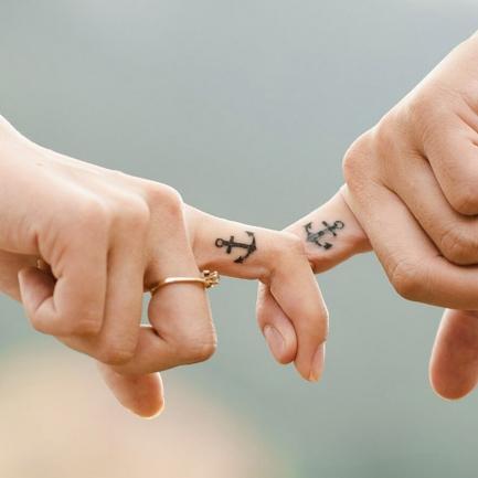Engagement - Manos tatuadas unidas por el dedo indice.