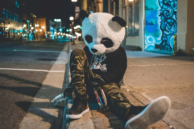 ho,bre con disfraz de oso panda sentado en la calle