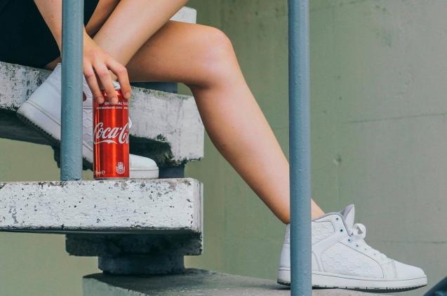 Detalle de las piernas de una chica sentada en una escalera abriendo lata de coca cola