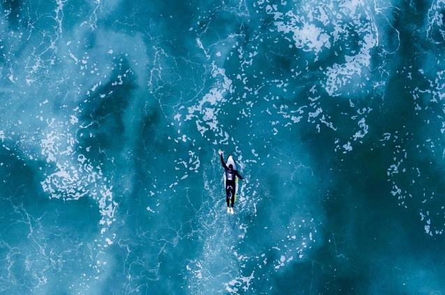 Surfista remando hasta la ola en medio del mar