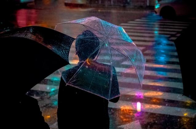 hombre bajo la lluvia con paraguas en la calle