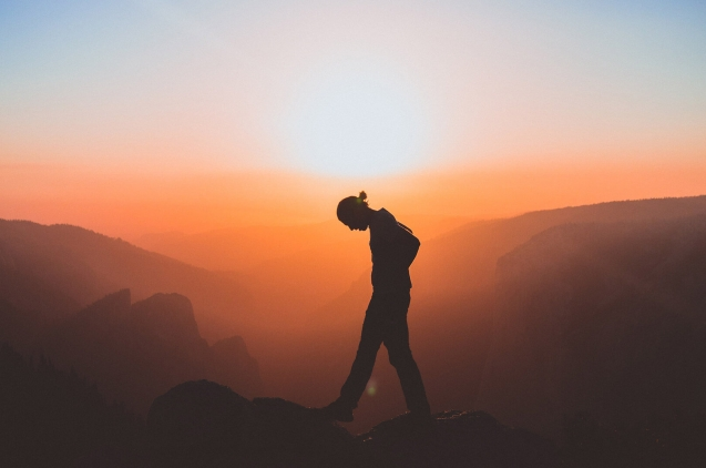 guy on the top of the mountain with sunset behind