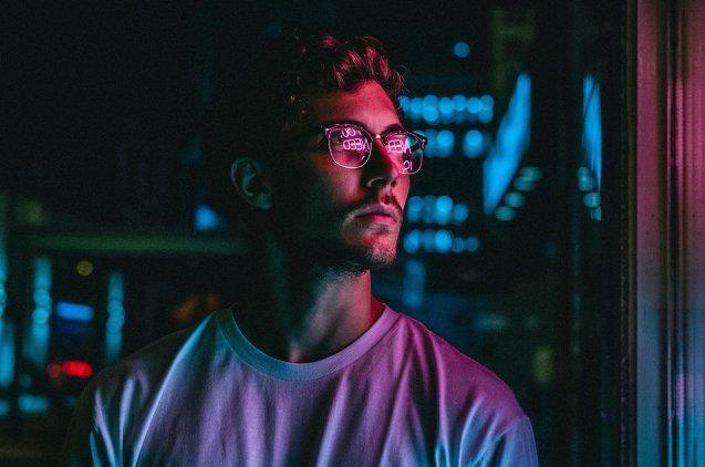 Chico mirando un escaparate con luces de neón