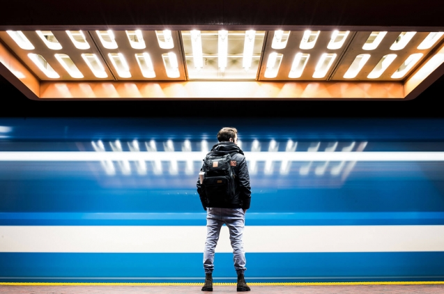 Person in front of a blue subway train